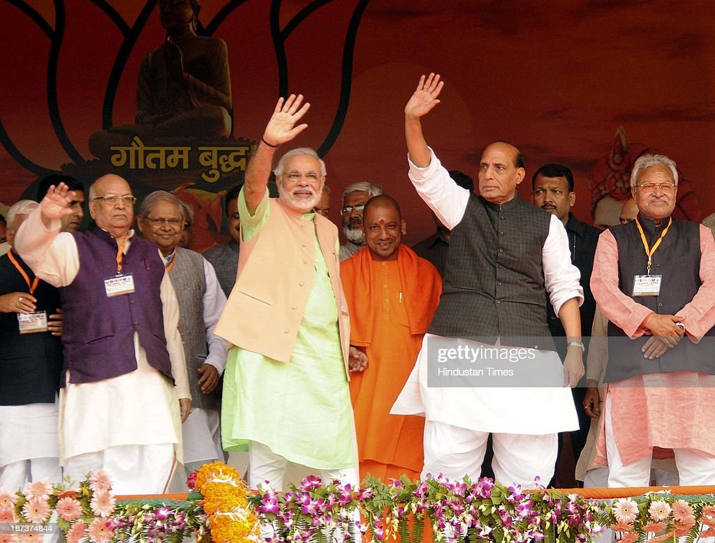 BJP prime ministerial candidate Narendra Modi and BJP President Rajnath Singh wave hands at the party's rally at Begumpur Sohrawa village on November 8, 2013 in Bahraich, India. In a hard-hitting attack on the Congress, Bahujan Samaj Party and Samajwadi Party at a rally here, Modi said the three parties had similar DNA, and urged people of Uttar Pradesh to give a decisive mandate to the BJP in the 2014 Lok Sabha polls.