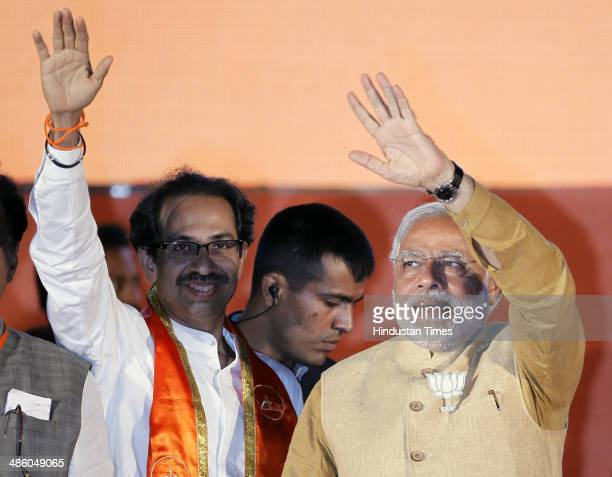 BJP prime ministerial candidate Narendra Modi waves to supporters with Shiv Sena party chief Uddhav Thackeray during an election rally at MMRDA...