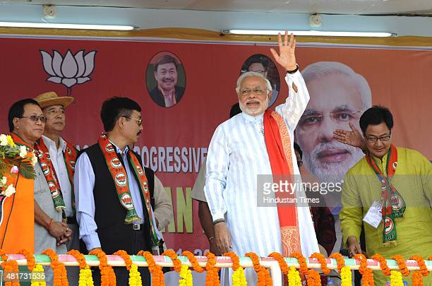 Prime Ministerial candidate Narendra Modi waves to the supporters during campaign rally for Lok Sabha election 2014 at Indira Gandhi Park on March 31...