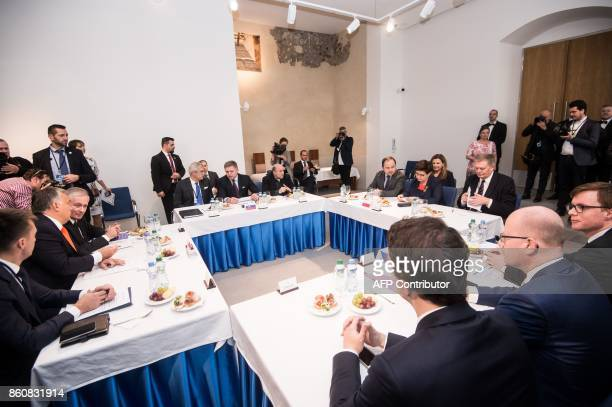 Prime ministers of the Visegrad group countries and their delegations sit at the round table during a Summit on Equal Quality of Products for All in...