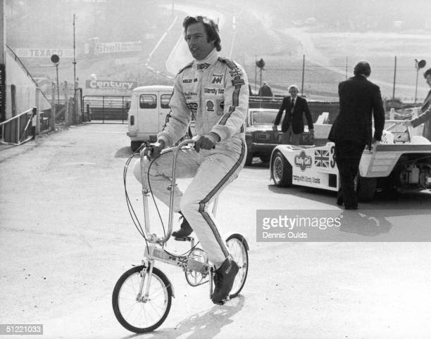 Prime Minister's son and erstwhile racing driver Mark Thatcher rides a folding bicycle to the pits at Brands Hatch racing circuit 28th February 1980