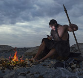 primitive man siting on the stone with smartphone