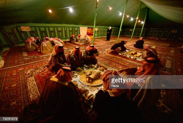 Prince Abdullah Bin Saad Bin Jilani Al Saoud serves a traditional meal of mutton to guests who arrive for a 'majlis' under his tent at the heart of...