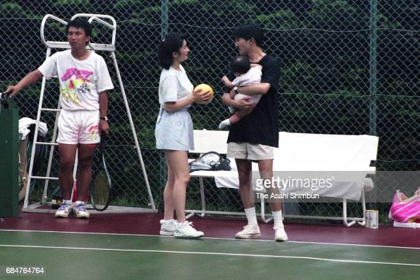 Prince Akishino holding his daughter Princess Mako talks with Princess Kiko on August 7 1992 in Karuizawa Nagano Japan