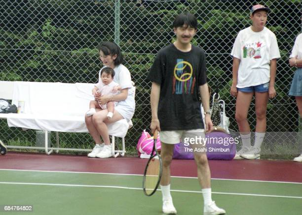 Prince Akishino plays tennis watched by Princess Kiko holding her daughter Princess Mako on August 7 1992 in Karuizawa Nagano Japan