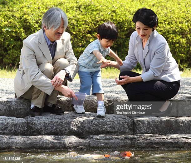 Prince Akishino Prince Hisahito and Princess Kiko of Akishino feed carps in a pond near the Hayama Imperial Villa on May 2 2009 in Hayama Kanagawa...