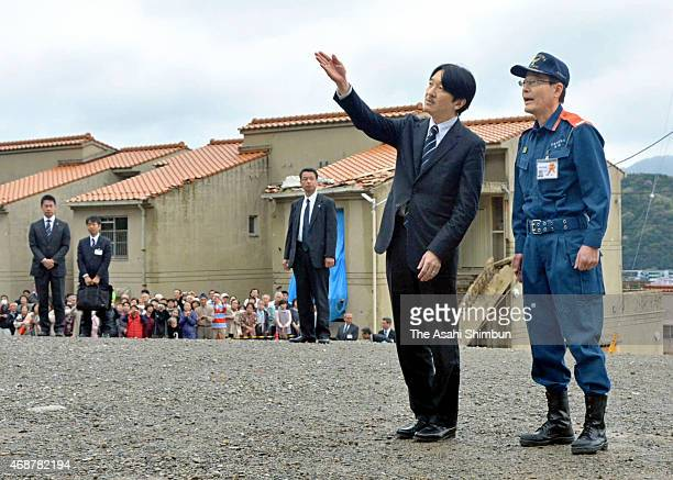 Prince Akishino speaks to a Hiroshima fire department officer at the landslide site on April 6 2015 in Hiroshima Japan The district was struck by a...