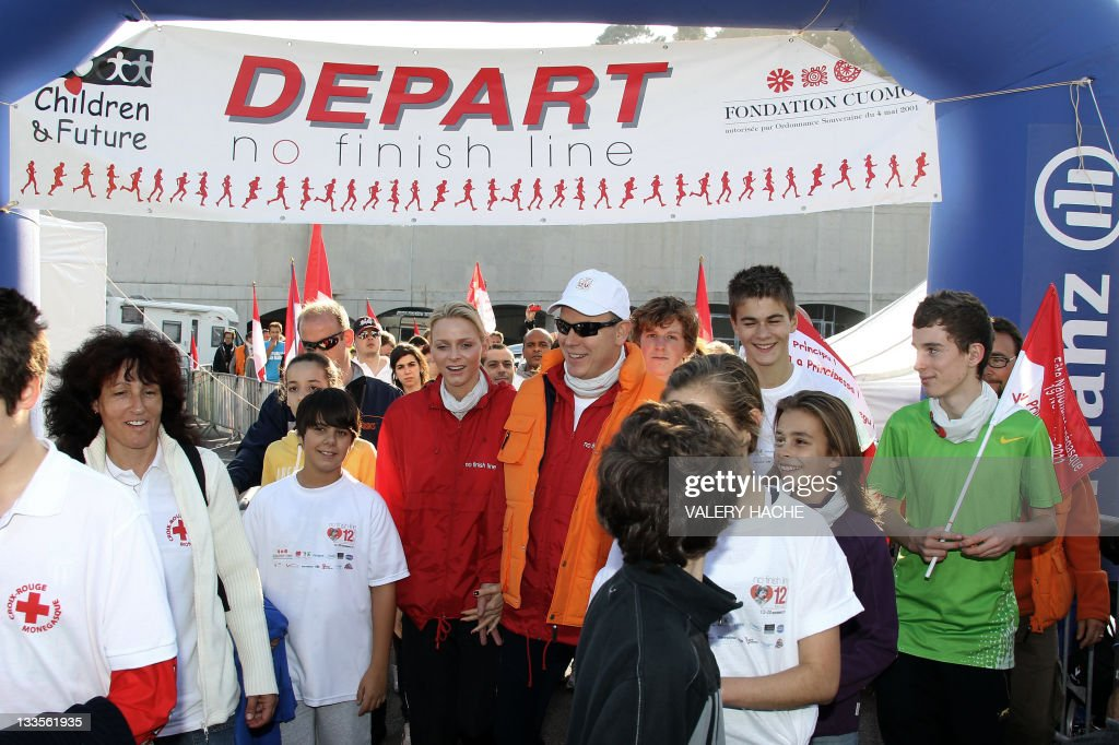 Prince Albert II (center, right) and princess Charlene of Monaco (center, left) pose with participants at the end of the 'No Finish Line' charitable running race, on November 20, 2011 in Monaco. Every kilometre completed, either by running or walking, means 1 euro donated to the nominated charities which include the Cardio-Thorasic Centre in Monaco, Fight AIDS Monaco, Hospital Cheick Zaied in Mauritius and the construction of a new school in Segou in Mali.