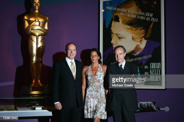 Prince Albert II of Monaco and his sister Princess Stephanie of Monaco stand in front of a poster featuring their late mother as Hollywood actress...
