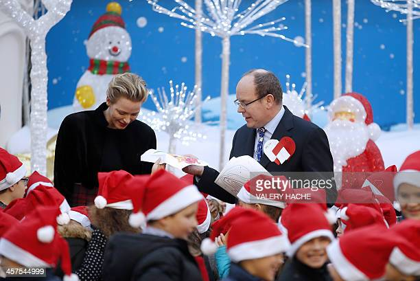 Prince Albert II of Monaco and his wife Charlene attend a Children's Christmas ceremony on December 18 2013 at the Monaco Palace AFP PHOTO / VALERY...