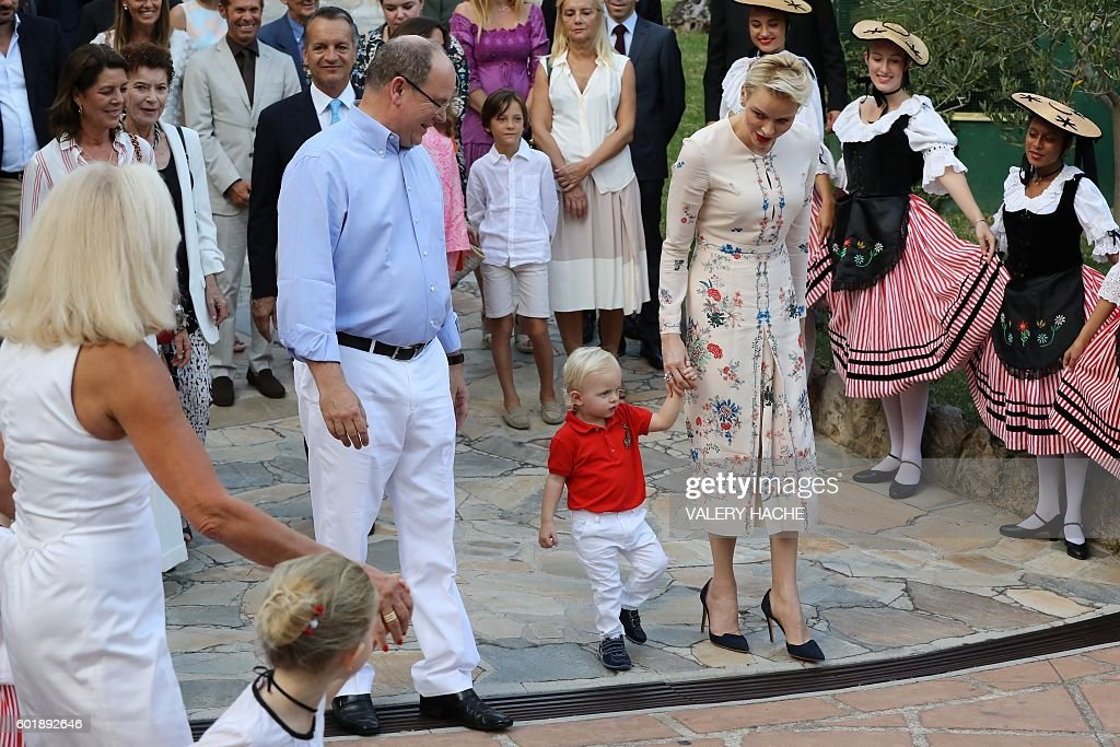 Prince Albert II of Monaco and his wife Charlene of Monaco attend a dance show with Prince Jacques, the heir apparent to the Monegasque throne during the traditional Monaco's picnic, on September 10, 2015 at Monaco. / AFP / POOL / VALERY