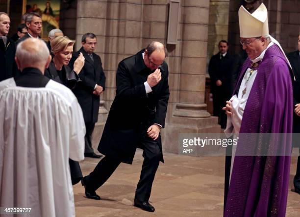 Prince Albert II of Monaco and his wife Princess Charlene make the sign of the cross as they arrive with Archbishop Bernard Barsi to attend an...