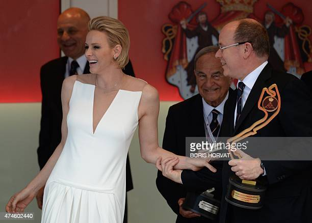 Prince Albert II of Monaco and his wife Princess Charlene share a laugh on the podium during the Monaco Formula One Grand Prix at the Monaco street...
