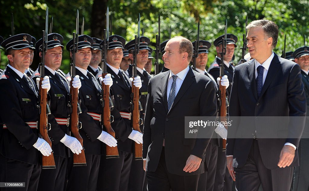 Prince Albert II of Monaco (C) and Montenegro's President Filip Vujanovic review a guard of honour prior to their meeting in Cetije on June 20, 2013. AFP PHOTO / SAVO PRELEVIC