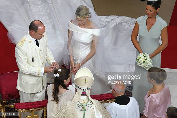 Prince Albert II of Monaco and Princess Charlene of Monaco exchange rings next to maid of honour Donatella Knecht de Massy during their religious...