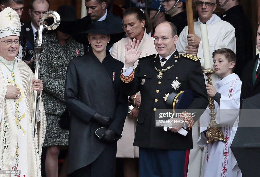 Prince Albert II of Monaco (first row, 2nd R) and princess Charlene of Monaco (first row, 2nd L) leave the cathedral after a mass during the celebrations marking Monaco's National Day, on November 19, 2013 in Monaco.