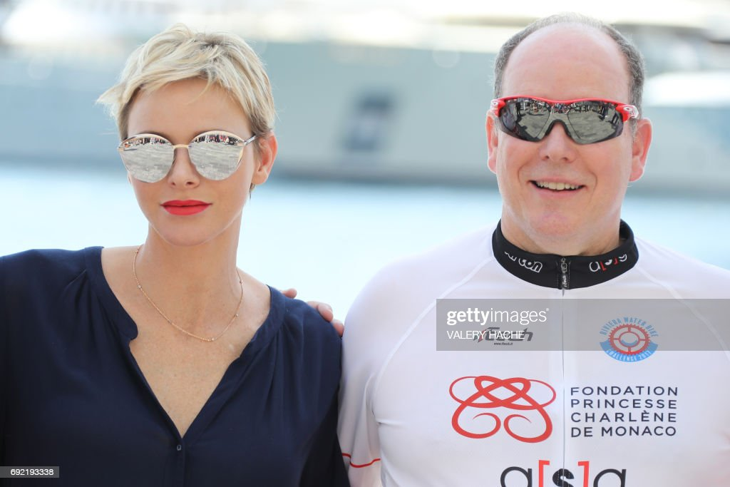 Prince Albert II of Monaco (R) and Princess Charlene of Monaco pose after attending the arrival of the first 'Riviera Water Bike Challenge', a water bike race between Nice and Monaco, in Monaco, on June 4, 2017. /