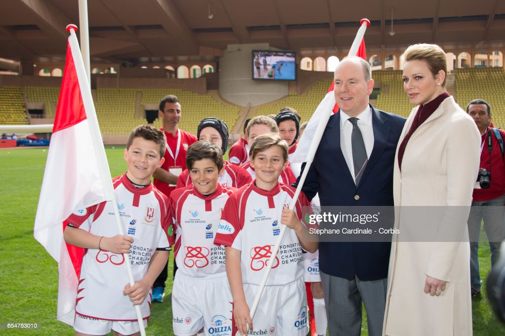 Prince Albert II of Monaco and Princess Charlene of Monaco pose with the Monaco Team during the Sainte Devote Rugby Tournament on March 18, 2017 in Monte-Carlo, Monaco.