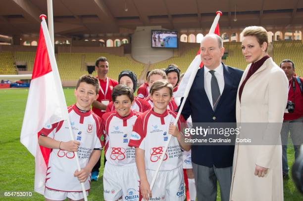 Prince Albert II of Monaco and Princess Charlene of Monaco pose with the Monaco Team during the Sainte Devote Rugby Tournament on March 18 2017 in...