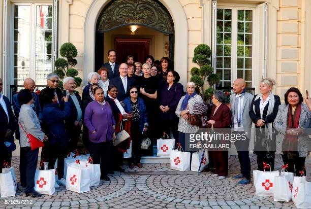 Prince Albert II of Monaco and Princess Charlene of Monaco pose with Monaco's residents during a Christmas giftgiving event at the headquarters of...