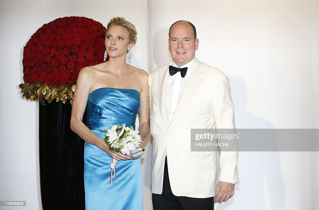 Prince Albert II of Monaco (R) and princess Charlene pose for photographers as they arrive to attend the 65th annual Red Cross Gala, on August 2, 2013, in Monaco. Created in 1948, the gala is an annual charity event held during the summer in Monaco by the Princely family.