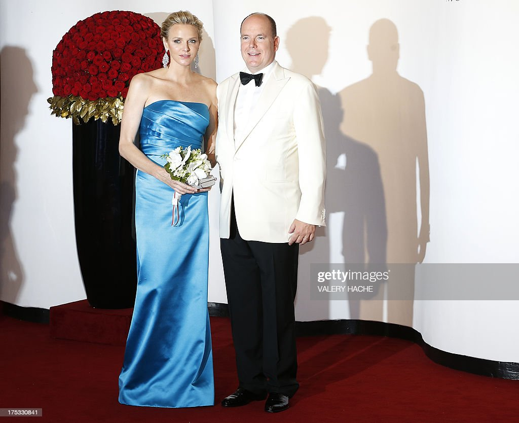 Prince Albert II of Monaco (R) and princess Charlene pose for photographers as they arrive to attend the 65th annual Red Cross Gala, on August 2, 2013, in Monaco. Created in 1948, the gala is an annual charity event held during the summer in Monaco by the Princely family. AFP PHOTO / VALERY HACHE