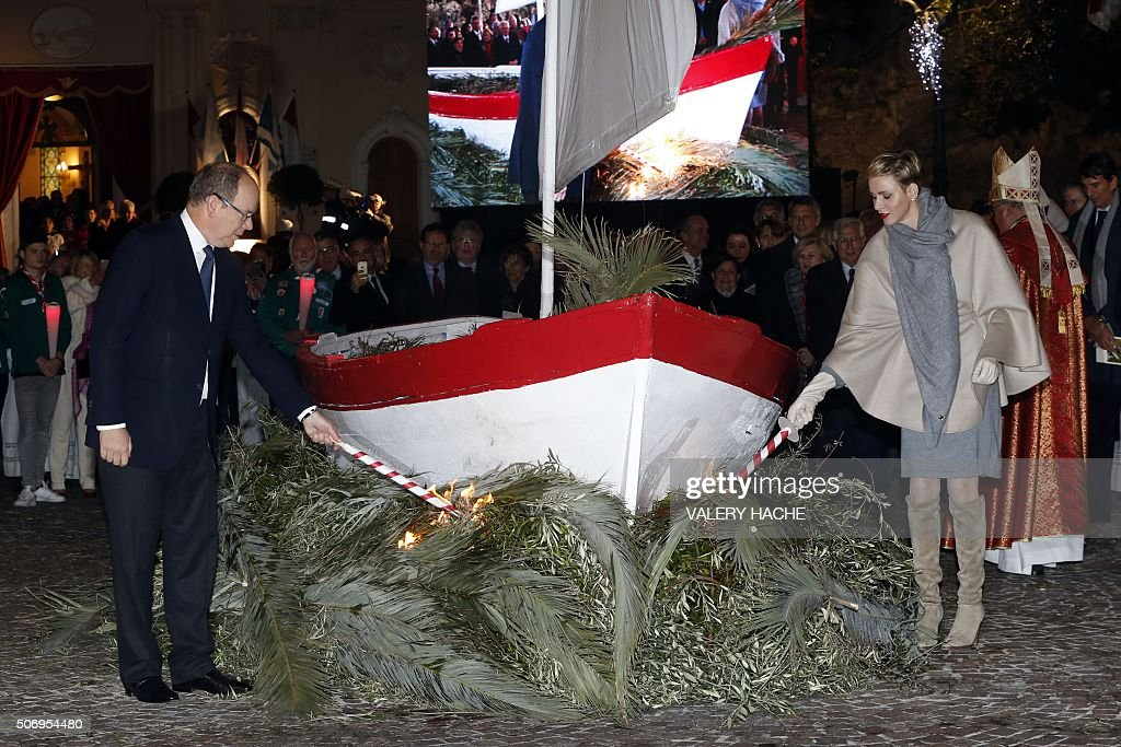 Prince Albert II of Monaco (L) and Princess Charlene (R) set symbolically fire to a boat with torches, on January 26, 2016 in Monaco, during the 'Sainte-Devote' procession. Sainte devote is the patron saint of Monaco and France's Mediterranean Corsica island. / AFP / VALERY