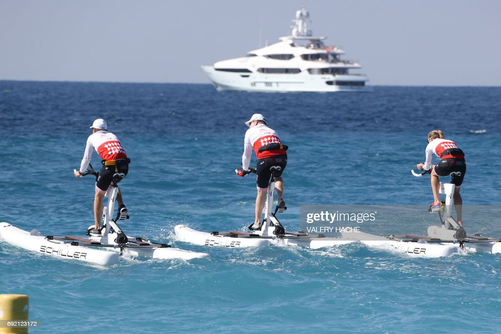 Prince Albert II of Monaco (C) competes in the first 'Riviera water bike challenge', a cycling race between Nice and Monaco, in Nice, southeastern France, on June 4, 2017. /