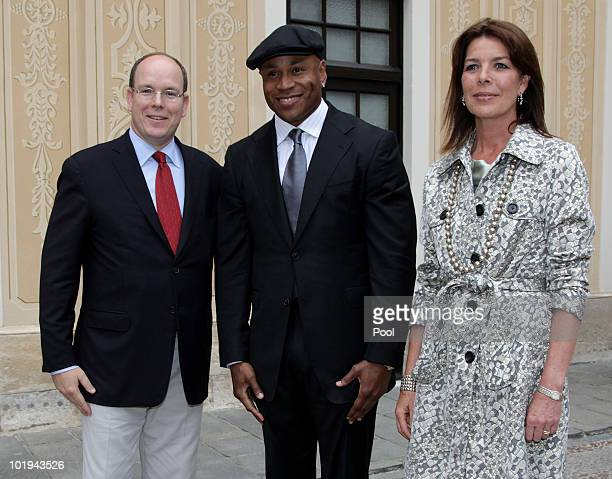 Prince Albert II of Monaco LL Cool J and Princess Caroline of Hanover pose as they attend a cocktail party in the courtyard of the Monaco Palace on...