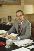 Prince Albert II of Monaco poses at his desk next to his trophies at the Royal Palace in Monaco December 1983 in Monte Carlo Monaco