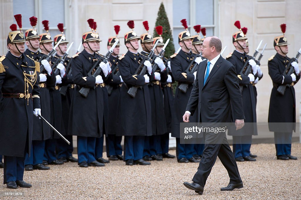 Prince Albert II of Monaco reviews the troops as he arrives before a lunch with France's President at the Elysee presidential palace in Paris on December 7, 2012. AFP PHOTO BERTRAND LANGLOIS