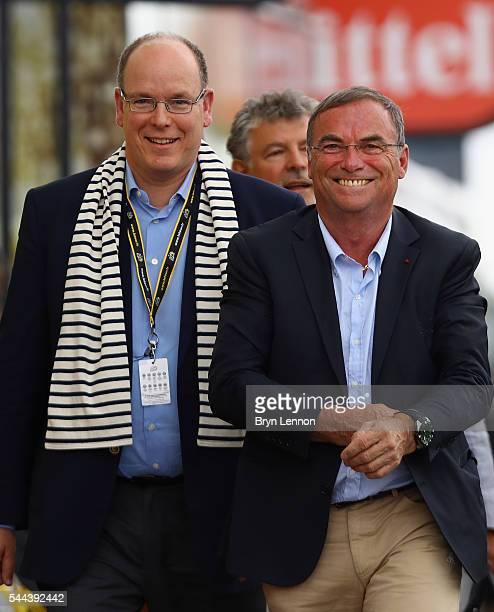 Prince Albert II of Monaco shares a joke with 5 times Tour de France winner Bernard Hinault of France prior to the podium presentation on stage two...