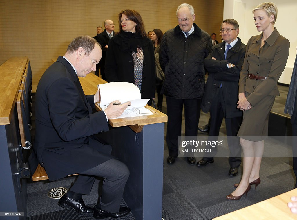 Prince Albert II of Monaco (L) sits in a seat in a classroom as he and Princess Charlene (R) visit the new 'Lycee Technique et Hotelier de Monaco' (Vocational school for hotel and catering) on February 20, 2013 in Monaco.