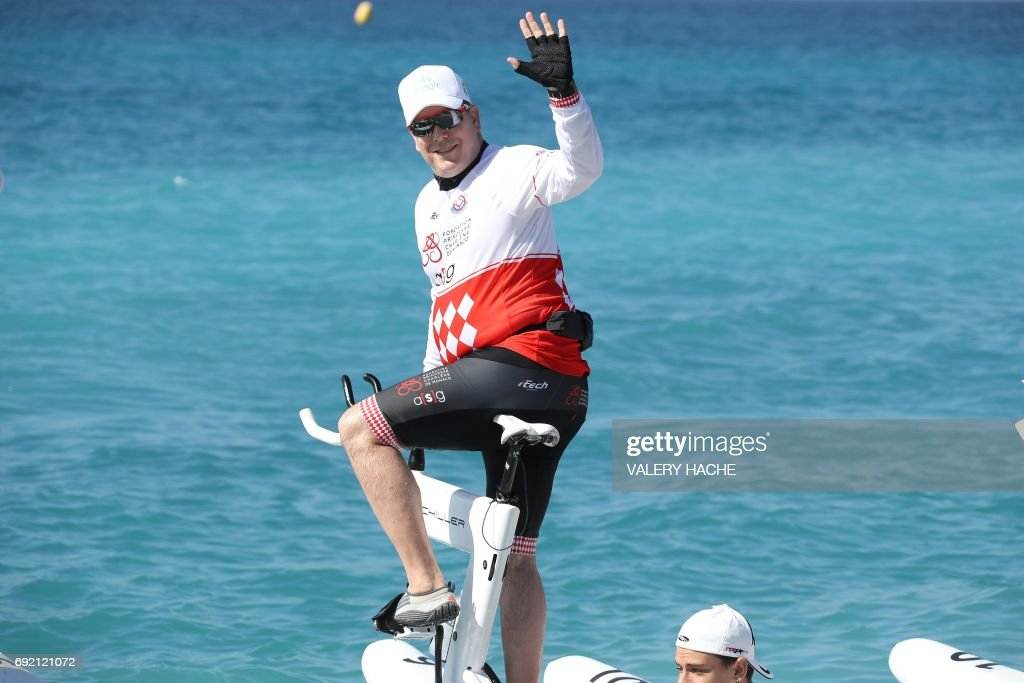 Prince Albert II of Monaco waves as he prepares to compete in the first 'Riviera water bike challenge', a cycling race between Nice and Monaco, in Nice, southeastern France, on June 4, 2017. /