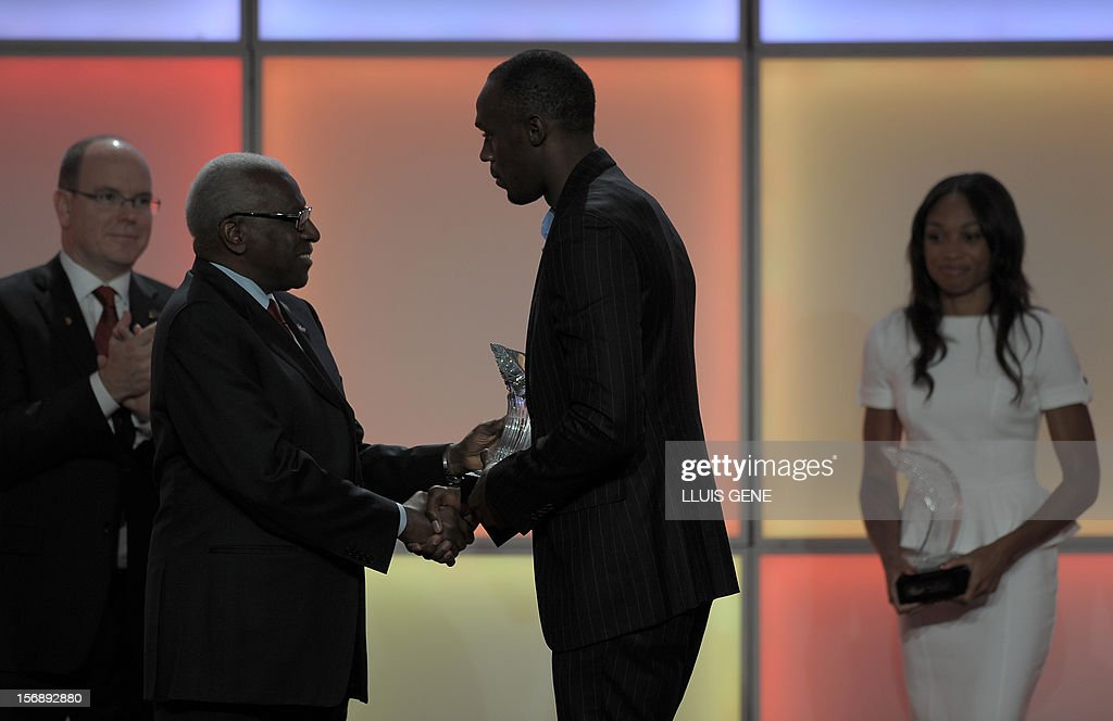 Prince Albert of Monaco applauds as IAAF (International Association of Athletics Federations) President Lamine Diack handovers IAAF´s Athlete of the Year trophy to Jamaican athlete Usain Bolt under the look of US sprinter Allyson Felix duriing the IAAF´s Athlete of the Year Award marking its centenary on November 24, 2012 in Barcelona.