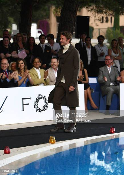 Prince Albert of Monaco Liz Hurley Arun Nayar and David Furnish watch as Jenson Button walks down the catwalk during the Grand Prix and Fashion Unite...