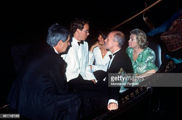 Prince Alberto of Monaco in white smoking is photographed on a gondola with Gaea Pallavicini great lady of the Roman nobility wearing a green fancy...