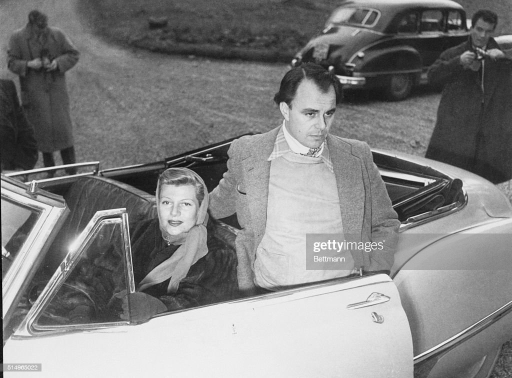 Prince Ali and His Rita Meet the Press. Dorigny, Switzerland: Glowering Prince Ali Khan and his wife, movie star <a gi-track='captionPersonalityLinkClicked' href=/galleries/search?phrase=Rita+Hayworth&family=editorial&specificpeople=70013 ng-click='$event.stopPropagation()'>Rita Hayworth</a>, pose in Rita's yellow convertible outside one of the Aga Khan's castles in Dorigny as they held a press conference early this week. Newsmen have been on the alert to flash the news of the birth of Rita's expected baby. They were told that the baby will not arrive until February, given champagne and told to go home to their folks for Christmas.