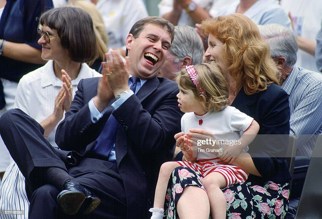 Prince Andrew And Sarah, Duchess Of York Sit Laughing With Princess Eugenie On Her Lap. They Are Attending The School's Sports Day
