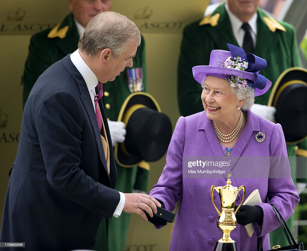 Prince Andrew, Duke of York presents his mother Queen Elizabeth II with the Gold Cup after her horse Estimate won the feature race on Ladies Day of Royal Ascot at Ascot Racecourse on June 20, 2013 in Ascot, England.