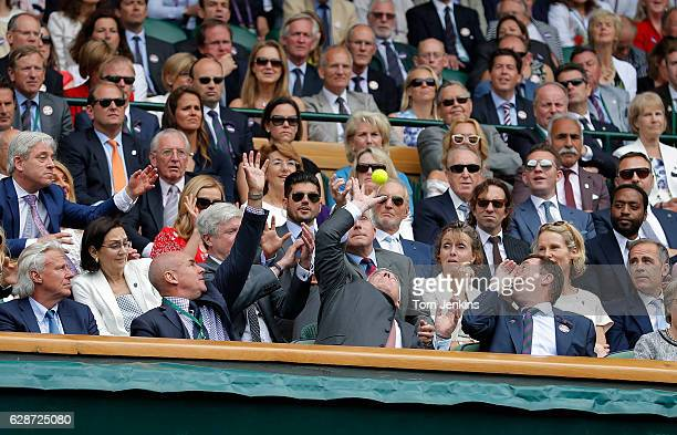 Prince Andrew tries to catch a ball deflected into the Royal Box during the Roger Federer v Milos Raonic semifinal on Centre Court during day eleven...