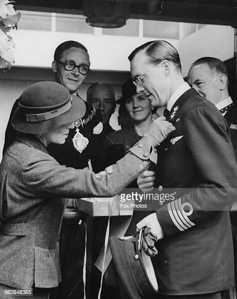 Prince Bernhard of the Netherlands buying a flag from a sales woman as he attends a charity event at Derry Gardens Kensington London July 22nd 1941
