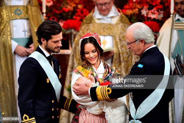 Prince Carl Philip princess Sofia and King Carl Gustaf of Sweden attend to baby with prince Gabriel during his christening in Drottningholm Palace...