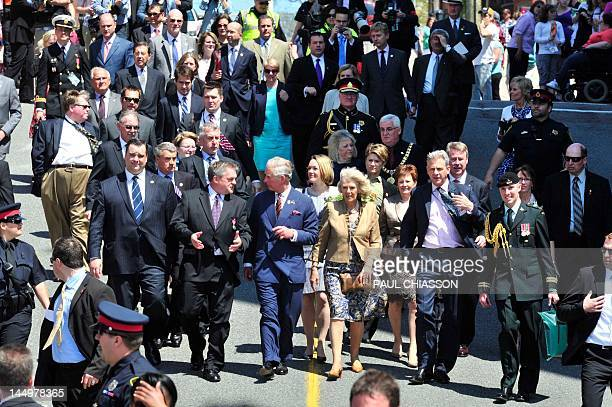Prince Charles alongside his wife Camilla talks with New Brunswick Premier David Alward along with Heritage Minister James Moore during a walk about...