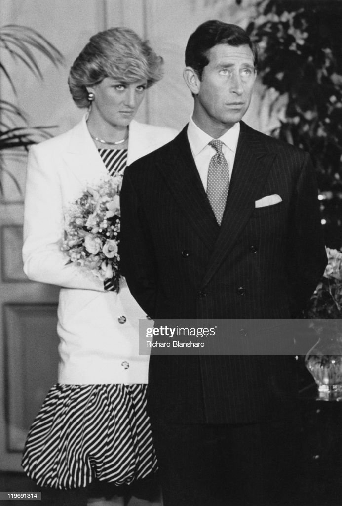 Prince Charles and Diana, Princess of Wales, attend the Cannes Film Festival, France, 15th May 1987. Diana is wearing a striped puffball dress with a white jacket.