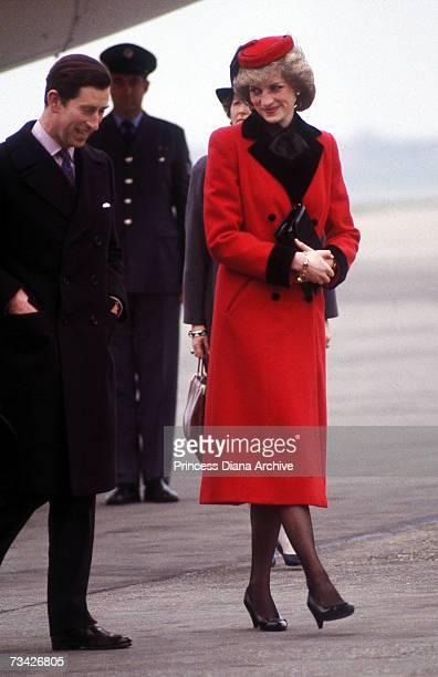Prince Charles and Princess Diana arrive at Birmingham Airport February 1984 The princess is wearing a red Catherine Walker coat with matching red...