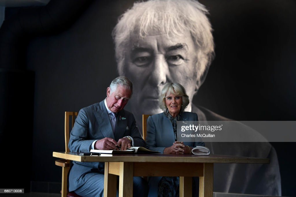 HRH Prince Charles and the Duchess of Cornwall sign the visitors book as they visit the Seamus Heaney Home Place on May 9, 2017 in Bellaghy, Northern Ireland. The arts and literary centre in Heaney's home town celebrates the late Poet Laureate's life and work via an interactive exhibition, aretfacts, photographs and manuscripts. The Royal couple are on a two day visit to Northern Ireland.