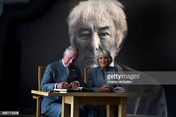 Prince Charles and the Duchess of Cornwall sign the visitors book as they visit the Seamus Heaney Home Place on May 9 2017 in Bellaghy Northern...