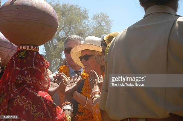 Prince Charles and wife Camilla Parker discussing with the ladies assembled for collecting water with their earthen pots near a water tank in their...
