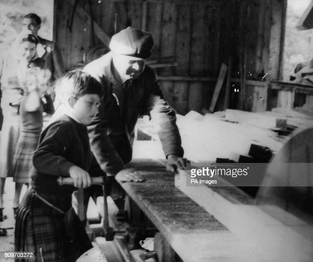Prince Charles being shown how to use a sawmill on the Balmoral Estate as Princess Anne covers her ears in the background with her mother Queen...